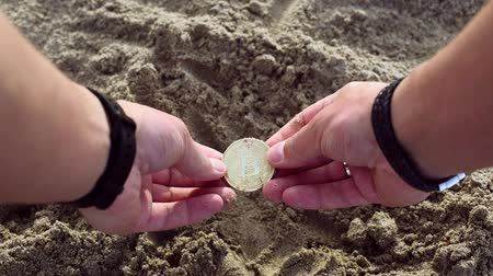 buried : Male hands dig in sand and find gold bitcoin Stock Footage