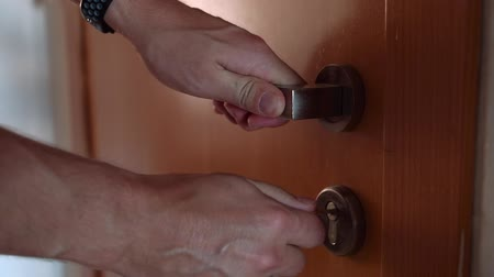 destravar : Close-up of male hands turning the key to lock the home door