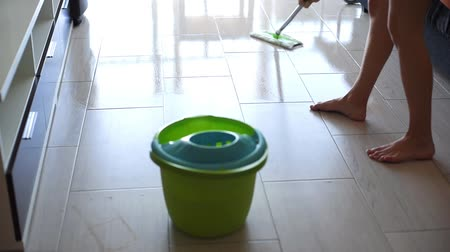 mopping : Young woman wiping white tile floor with mop at home