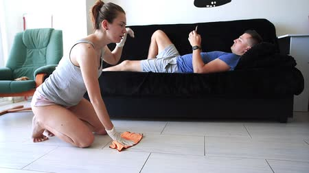 Tired wife cleans the tile floor while her husband lies on the couch