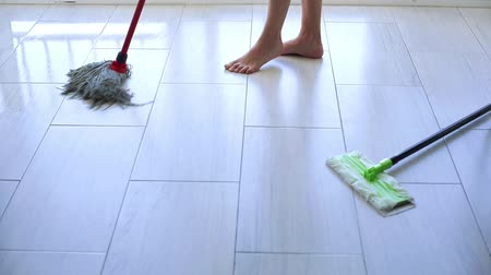 Young woman wiping white tile floor with mop at home
