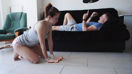 slave : Tired wife cleans the tile floor while her husband lies on the couch