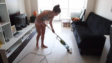 держит : Young attractive housewife vacuuming in the room Стоковые видеозаписи