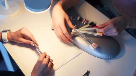 Close-up of female clients hands choosing color for manicure