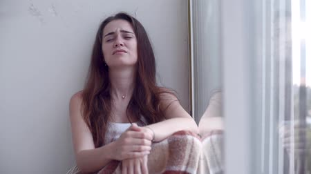 discomfort : Depressed woman crying by the window Stock Footage