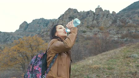 copo : Woman tourist with backpack drinking water in nature.Crimea