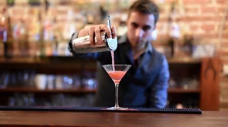 nápoj : barman preparing and pouring cosmopolitan alcoholic cocktail drink at bar. Alcoholic drink with vodka, triple sec, cranberry juice and lemon juice