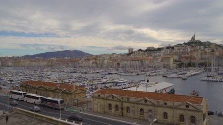 docked : MARSEILLE, FRANCE - 10 Nov 2018 - The Old Port Vieux Port of Marseille with Basilique Notre-Dame de la Garde at the background inn 4k Stock Footage