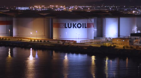 inflamável : BARCELONA, SPAIN - NOVEMBER 09, 2018 - Lukoil oil storage tanks or containers in the harbour of the city in 4k