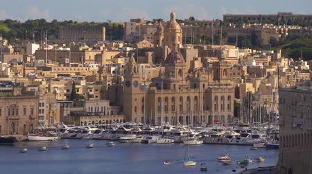 мальтийский : VALLETTA, MALTA - NOVEMBER 12, 2018 - The coastline of Isla Birgu island with harbour, cruise ship, boats and panorama of the city in 4k