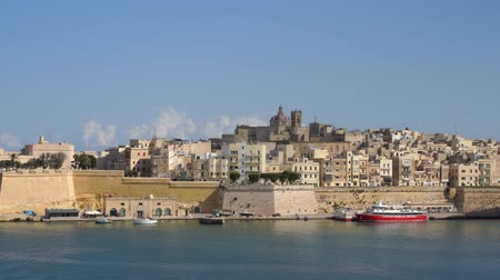 мальтийский : VALLETTA, MALTA - NOVEMBER 12, 2018 - The waterfront of Isla Birgu island with harbourboats and panorama of Fort St. Angelo