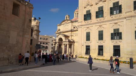 век : VALLETTA, MALTA - NOVEMBER 12, 2018 - Exterior view of the Auberge de Castille in Castille Square with people walking by in 4k