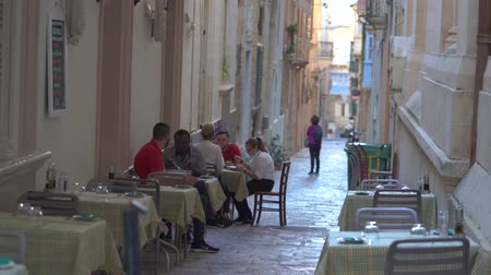 VALLETTA, MALTA - NOVEMBER 12, 2018 - People having dinner on the narrow streets in historical part of the city in 4k