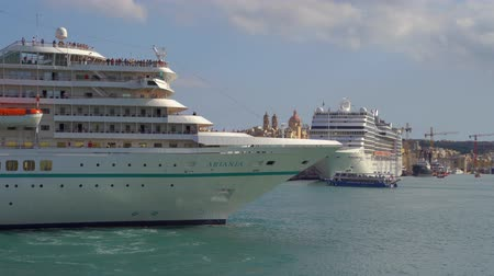 VALLETTA, MALTA - NOVEMBER 12, 2018 - Luxury cruise ship at the port of the city with panoramic view of the old ancient walls in 4k
