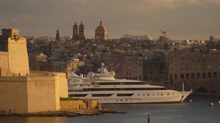 крейсерский : VALLETTA, MALTA - NOVEMBER 12, 2018 - Luxury cruise ship at the port of the city with panoramic view of the old ancient walls in 4k