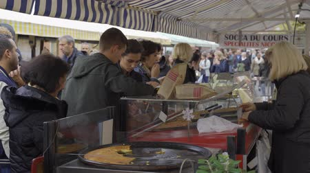 NICE, FRANCE - NOVEMBER 10, 2018 - People shopping at farmer market and a stall with variety of organic vegetable and fruit in 4k