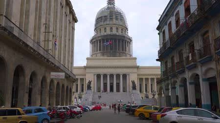 oszlopok : HAVANA, CUBA - MAY 13, 2018 - Street view of the dome of El Capitolio in Old city with people and cars in 4k Stock mozgókép