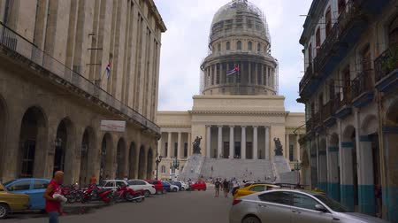 коммунизм : HAVANA, CUBA - MAY 13, 2018 - Street view of the dome of El Capitolio in Old city with people and cars in 4k Стоковые видеозаписи