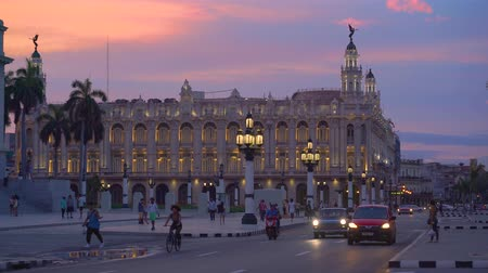 HAVANA, CUBA - MAY 13, 2018 - Panoramic street view of the Great Theatre of Havana in the sunset with vintage cars and people in 4k Dostupné videozáznamy