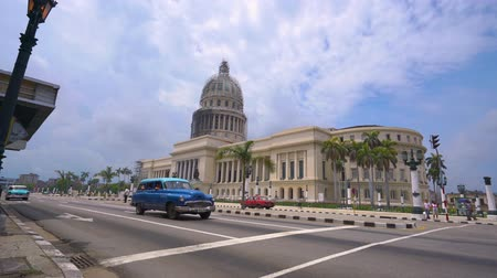 HAVANA, CUBA - MAY 13, 2018 - El Capitolio, or the National Capitol Building with vintage american cars and people on the streets in 4k Dostupné videozáznamy