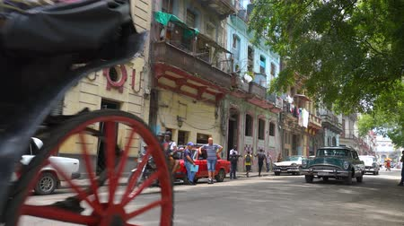 HAVANA, CUBA - MAY 13, 2018 - Horse carriage, people and old taxi cars on the streets in 4k