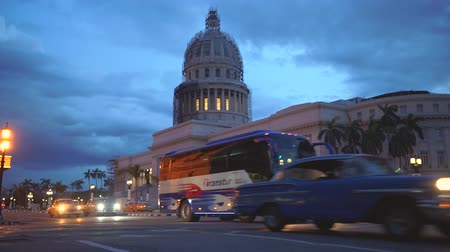 HAVANA, CUBA - MAY 13, 2018 - El Capitolio in sunset with vintage american cars and people on the streets in 4k