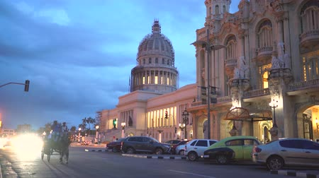 comunismo : HAVANA, CUBA - MAY 13, 2018 - El Capitolio in sunset with vintage american cars and people on the streets in 4k
