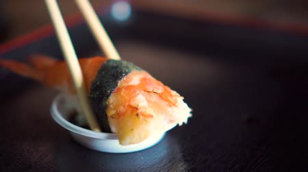 cozinha japonesa : A sushi with big shrimp and seaweed getting dip with shoyu sauce. Slow Motion. Stock Footage