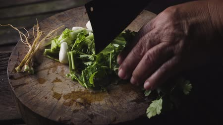 боа : Hands of an old lady chopping spring onion and coriander on a wooden cutting boa