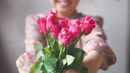 Asian lady with smile gives a bouquet of pink roses to you. for love one.