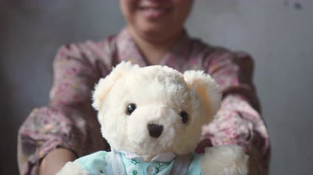 beer : Asian lady with smile gives a teddy with blue cloth to you. Valentines day.