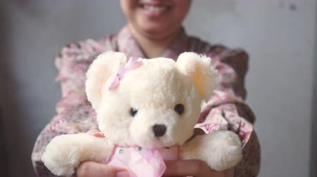 Asian lady with smile gives a teddy with pink cloth to you. Valentines day Stock Footage