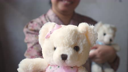 beer : Asian lady with smile gives a teddy with pink cloth to you. other in her arm. for love one. Valentines day.