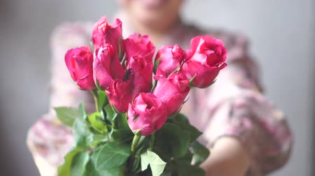 Asian lady with smile gives a bouquet of pink roses to you. Slow Motion
