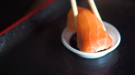 frescura : A sushi with salmon on top getting dip many times with shoyu sauce. Slow Motion. Vídeos