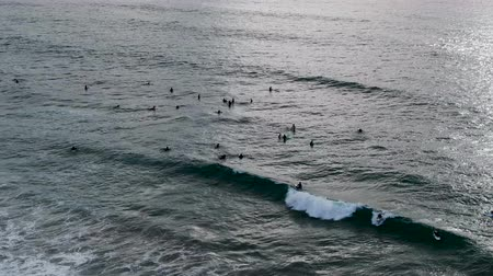 enrolar : Aerial view of surfers waiting, paddling and enjoying waves before sunset time during clouded day. Del Mar Beach, California, USA
