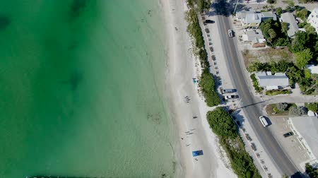 carolina : Aerial view of Coquina Beach with small pier, white sand beach and turquoise water in Bradenton Beach during blue summer day, Anna Maria Island, Florida. USA Stock Footage