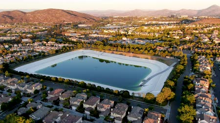 下位区分 : Aerial view of water recycling reservoir surrounded by suburban neighborhood with big villas during sunset time, South California