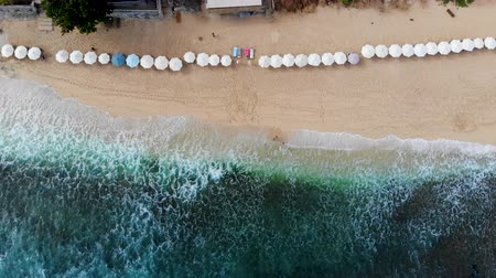 parasol : Aerial top view beach with sun parasol and turquoise sea with waves in Bali, Balangan Beach, Indonesia.