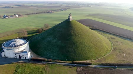bojiště : Aerial view of The Lions Mound with farm land around. The immense Butte Du Lion on the battlefield of Waterloo where Napoleon died. Belgium. Dostupné videozáznamy