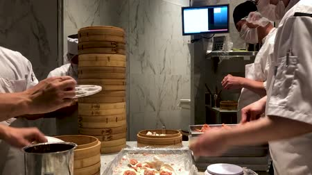 Chefs cooking Chinese dumplings by the traditional bamboo steamers in a restaurant. Dim Sum chefs working wrapping dumplings at famous restaurant Din Tai Fung. San Deigo, California, USA. February,07, 2020 Стоковые видеозаписи