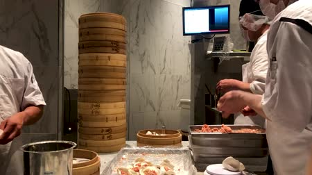 prawns : Chefs cooking Chinese dumplings by the traditional bamboo steamers in a restaurant. Dim Sum chefs working wrapping dumplings at famous restaurant Din Tai Fung. San Deigo, California, USA. February,07, 2020 Stock Footage