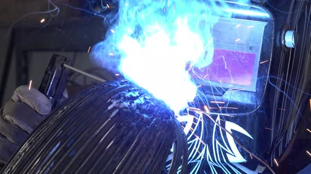 spawacz : a sculptor working on His arc welding and metal parts statuetwisting