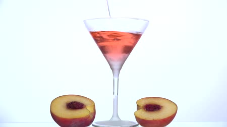curacao : Pouring peach liqueur in a frosted peach halves glassTwo near glass with white background Stock Footage