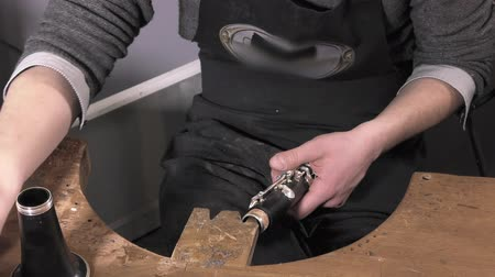 clarinet : a craftsman repairing an old clarinet