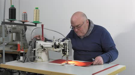 Man sewing pieces of leather