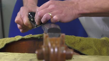 luthier shapes ebony fingerboard with a wood planer Stock Footage