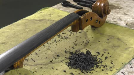 pétala : luthier shapes ebony fingerboard with a wood planer Stock Footage