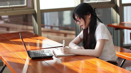 középiskola : Asian girl in uniform studying in library Stock mozgókép