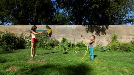 quintal : Two happy sisters playing with garden watering in the backyard
